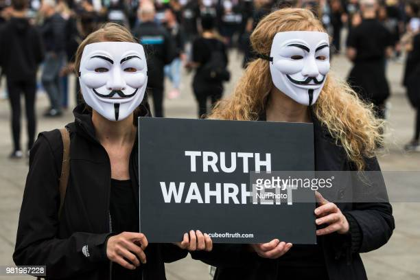 Activists wearing the mask of Anonymous attend a '24 Hours of Truth' action at Alexanderplatz in Berlin Germany on June 23 2018 Demonstrators want to...