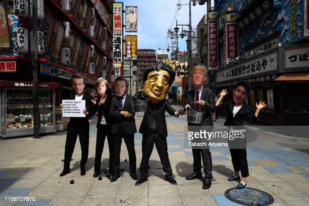 Activists with a French President Emmanuel Macron mask, Germany Federal Chancellor Angela Merkel mask, South Korean President Moon Jae-in mask,...