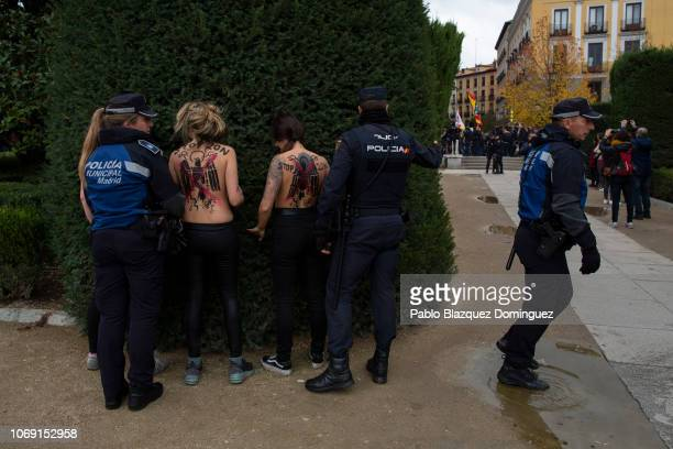 FEMEN activists with body painting reading 'Stop 20N' are secured by police officers after they protested against fascism during a rally...