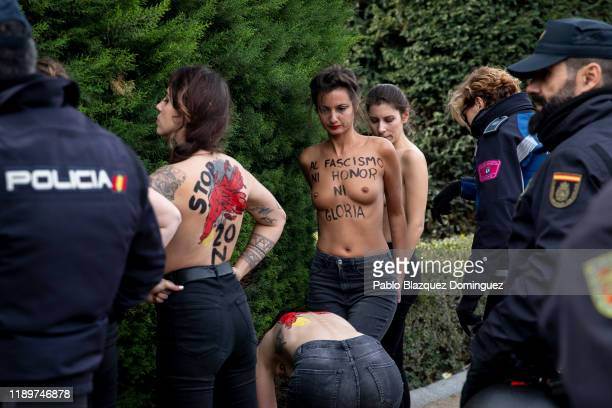 FEMEN activists with body painting reading 'To fascism neither honor nor glory' are retained by police after they protested during a rally...