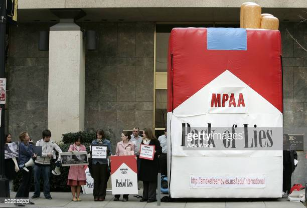 Activists with Essential Action hold posters next to a giant inflatable cigarette pack during a protest against movies that promote smoking to kids...
