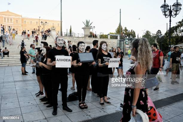 Activists with face masks are seen holding posters during the demonstration Anonymous for the voiceless protest by the vegan activists on Syntagma...