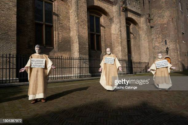 Activists with posters denouncing policies that lead to environmental degradation and climate change, during the performance in The Hague on February...
