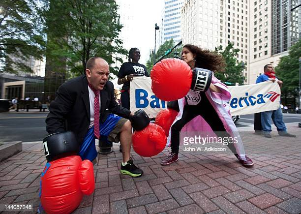 Activists with the 99 Percent Spring movement perform a boxing routine outside of the annual Bank of America Corp shareholders meeting on May 9 in...