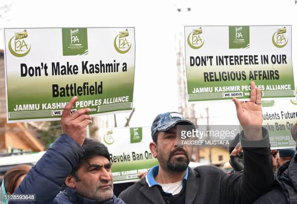 Activists with the Jammu Kashmir Peoples Alliance hold placards during a protest against the JamaateIslami ban in Srinagar on March 4 2019 Indian...