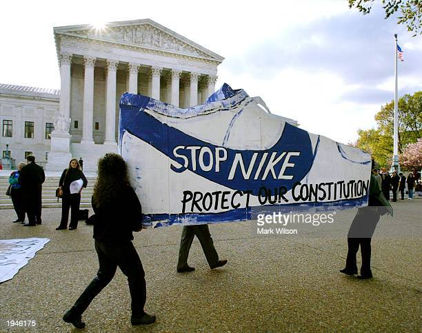Activists with the Sierra Club carry a sign shaped like a Nike sneaker as the sun rises over the US Supreme Court April 23 2003 in Washington DC The...