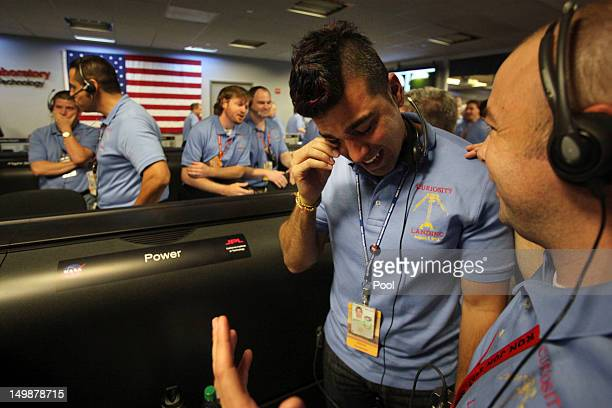 Activity lead Bobak Ferdowsi, center, wipes tears away after a successful landing inside the Spaceflight Operations Facility for NASA's Mars Science...