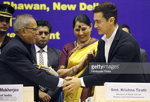 Actor Aamir Khan shaking hands with Indian President Pranab Mukherjee as Women and Child Development Minister Krishna Tirath looks on during the...