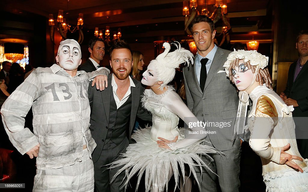 Actor Aaron Paul (2nd L) and Arizona Cardinals linebacker Stewart Bradley (2nd R) appear with 'Zarkana by Cirque du Soleil' characters at the reception for the Las Vegas premiere of 'Zarkana by Cirque du Soleil' at the Gold Boutique Nightclub and Lounge at the Aria Resort & Casino at CityCenter on November 9, 2012 in Las Vegas, Nevada.
