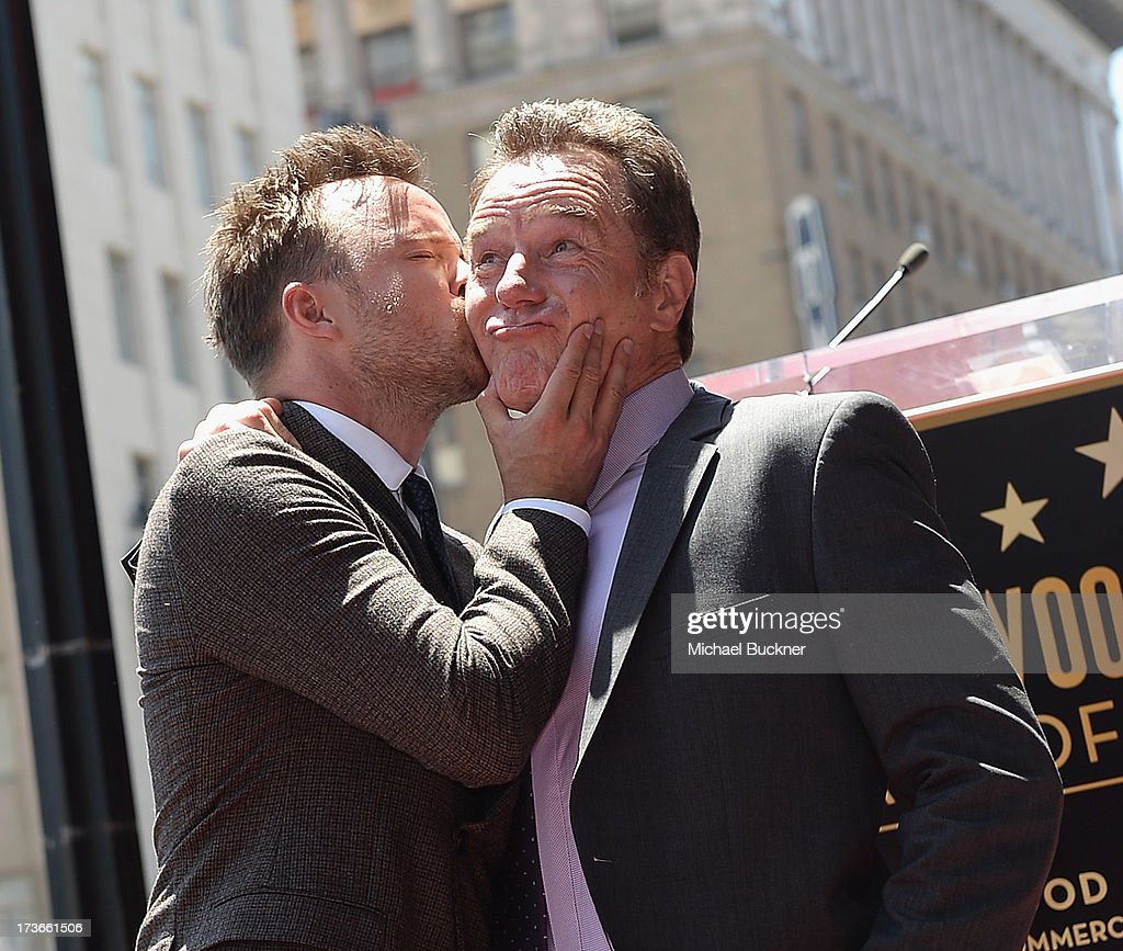 Actor Aaron Paul (L) kisses actor Bryan Cranston on the Hollywood Walk of Fame on July 16, 2013 in Hollywood, California.