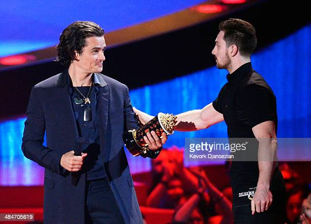 Actor Aaron TaylorJohnson presents the Best Fight award for 'The Hobbit The Desolation of Smaug' to actor Orlando Bloom onstage at the 2014 MTV Movie...