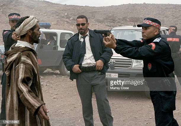 Actor Abdelkader Bara as Hassan is questioned by Driss Roukhe as federal policeman Alarid and his officers in a scene from the movie 'Babel' being...