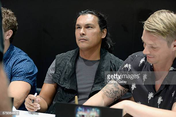 Actor Adam Beach and Joel Kinnaman from the cast of Suicide Squad film participates in an autograph session for fans in DC's 2016 ComicCon booth at...