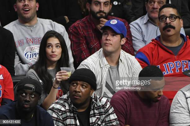 Actor Adam Devine and Chloe Bridges attend a basketball game between the Los Angeles Clippers and the Houston Rockets at Staples Center on January 15...