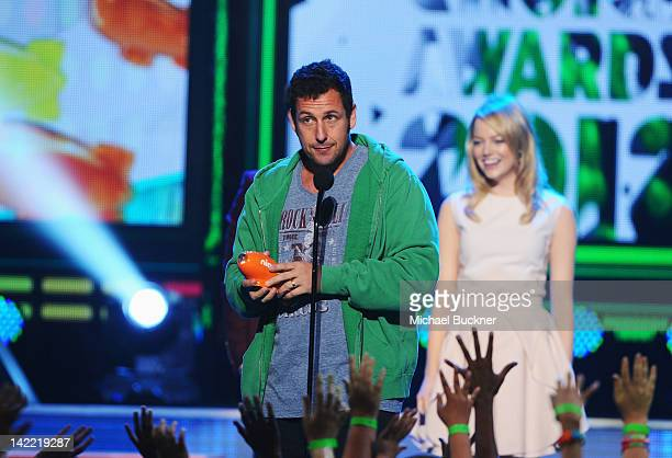 Actor Adam Sandler accepts the Favorite Movie Actor award from presenter Emma Stone onstage at Nickelodeon's 25th Annual Kids' Choice Awards held at...