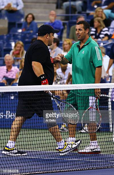 Actor Adam Sandler bumps fists with comedian Kevin James during a celebrity doubles match on Day Eleven of the 2012 US Open at USTA Billie Jean King...