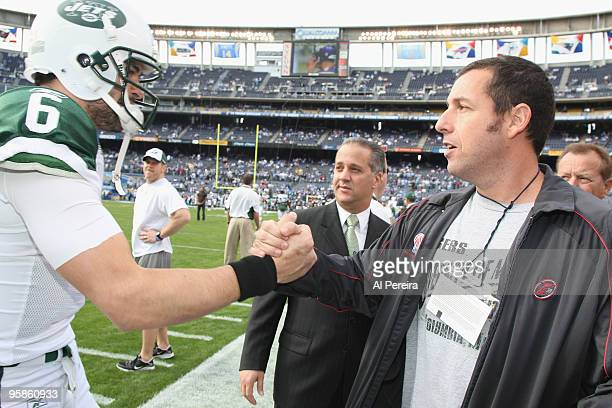 Actor Adam Sandler meets with Quarterback Mark Sanchez of the New York Jets on the sideline before the start of the AFC Divisional Playoff game...