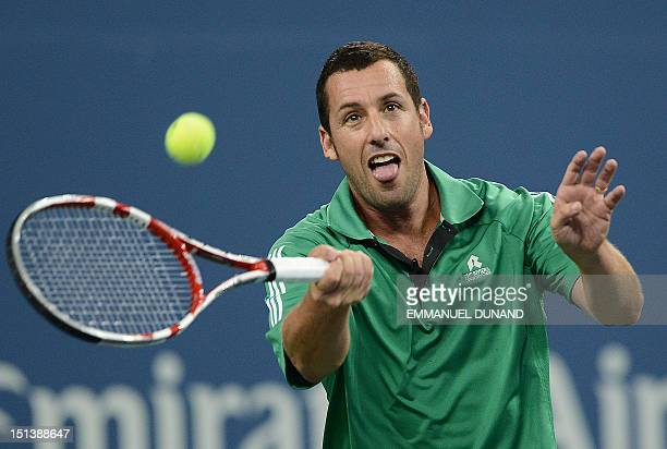 Actor Adam sandler plays a point while pairing with John McEnroe against Jim Courier and Kevin James during an exhibition match at the 2012 US Open...
