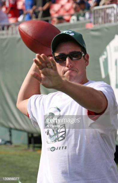 Actor Adam Sandler tosses a football in action on the Jets' sideline during the Patriots' 2417 win over the New York Jets at the Meadowlands Eat...