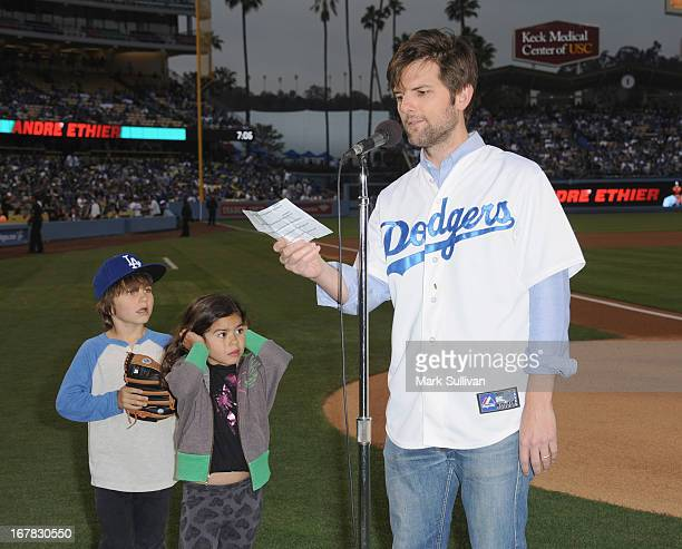 Actor Adam Scott with his children reads the Dodger starting lineup before the game between the Los Angeles Dodgers and Denver Rockies at Dodger...