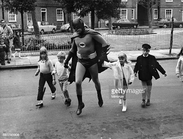 Actor Adam West who plays Batman, the Caped Crusader of Gotham City, helping children cross the road while making a one-minute road safety film for...