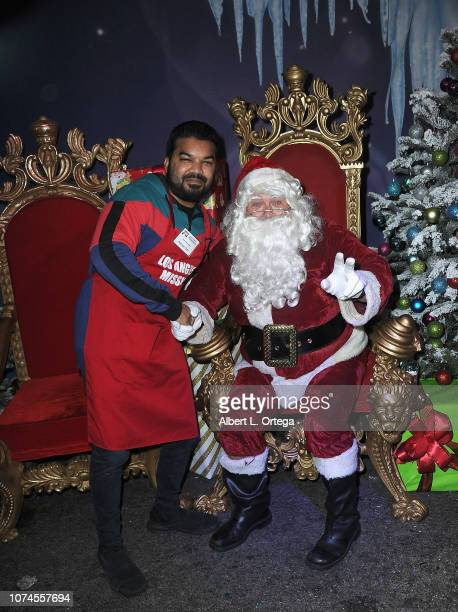 Actor Adrian Dev poses with Santa Claus at the Los Angeles Mission Christmas On Skid Row held at Los Angeles Mission on December 21 2018 in Los...