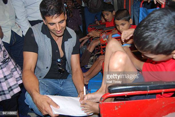 Actor Akhay Kumar interacts with physically challenged children at a special screening of the film De Dana Dan in Mumbai on Saturday December 5 2009