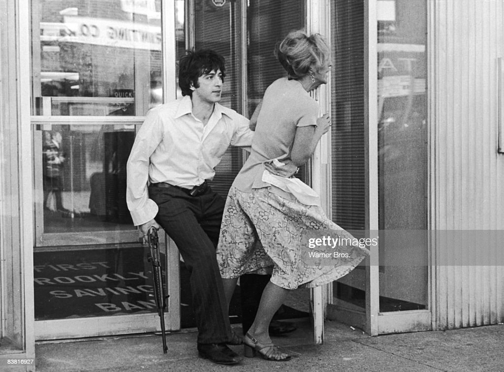 Actor Al Pacino tries to drag Penelope Allen into a bank during a robbery, in a still from the film 'Dog Day Afternoon', directed by Sidney Lumet, 1975.