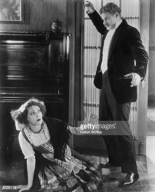 Actor Alan Hale menaces Alla Nazimova as she kneels on the floor in a still from the film 'A Doll's House' directed by Charles Bryant and adapted...