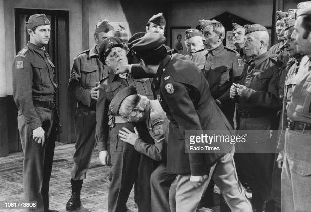 Actor Alan Tilvern punching Robert Raglan in the face as Clive Dunn ducks for cover watched by actors Ian Lavender and John Le Mesurier in a scene...