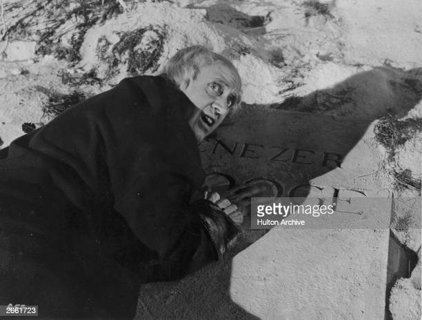 Actor Alastair Sim as Ebenezer Scrooge crouched in terror over his own gravestone in the film 'Scrooge' directed by Brian Desmond Hurst for Renown