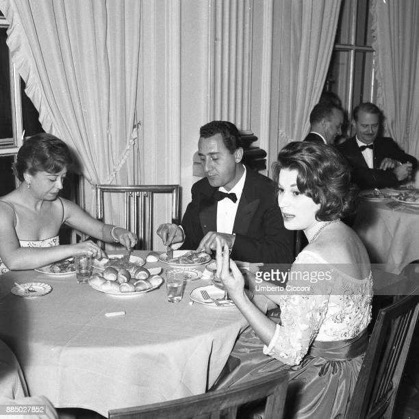 Actor Alberto Sordi and actresses Silvana Mangano and Giulietta Masina at the dinner party for the movie 'The Tempest' Italy 1958