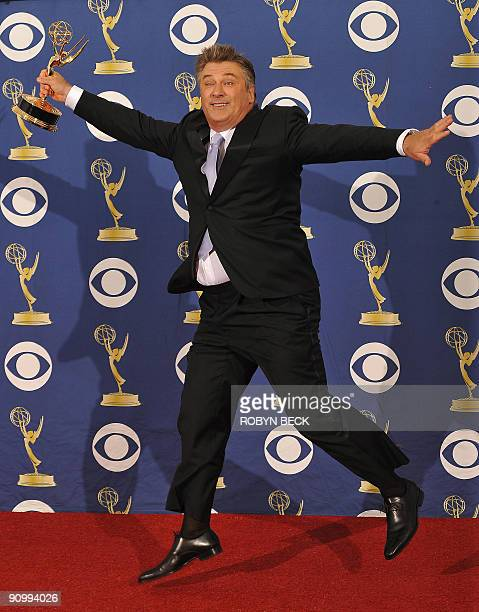 Actor Alec Baldwin from the TV show '30 Rock' leaps as he holds the the Best Actor in a Comedy award in the press room during the 2009 Emmy Awards at...