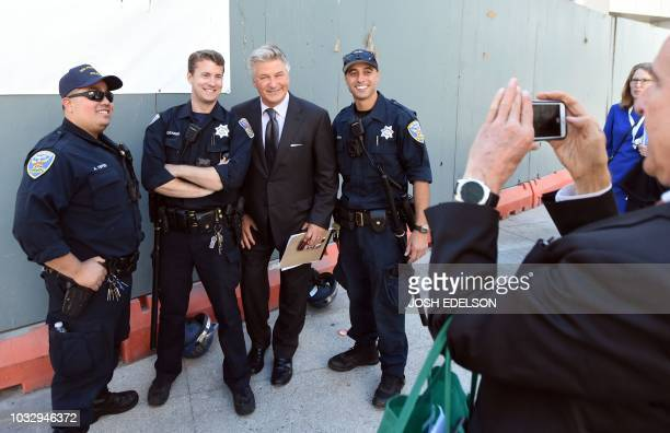 Actor Alec Baldwin poses for a photo with local police officers in San Francisco California outside the Global Climate Action Summit on September 13...