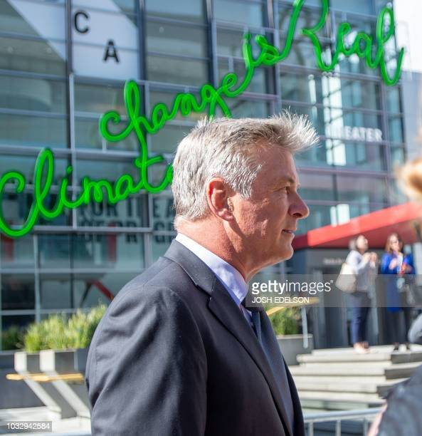 Actor Alec Baldwin walks in front of a neon sign proclaiming the validity of climate change in San Francisco California on September 13 2018