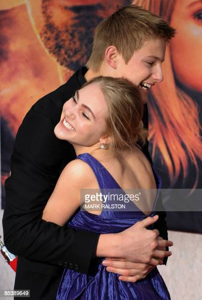 Actor Alexander Ludwig hugs costar AnnaSophia Robb as they arrive for the world premiere of the Disney film 'Race to Witch Mountain' at the El...