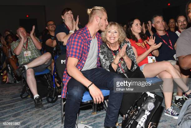 Actor Alexander Ludwig kisses fan Gayann Greene of California after he went into the audience to watch a clip of his show 'Vikings' during ComicCon...