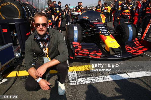 Actor Alexander Skarsgard poses for a photo with the car of Max Verstappen of Netherlands and Red Bull Racing on the grid before the F1 Grand Prix of...