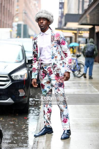 Actor Al-Teron Williams is seen wearing a floral suit, light pink shirt, dark blue shoes and grey fur hat outside of the Alice + Olivia By Stacey...
