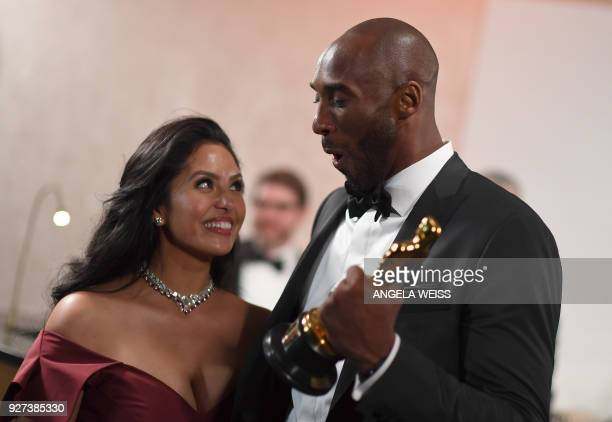 TOPSHOT US actor and basketball player Kobe Bryant holds an oscar beside his wife Vanessa Laine Bryant during the 90th Annual Academy Awards on March...