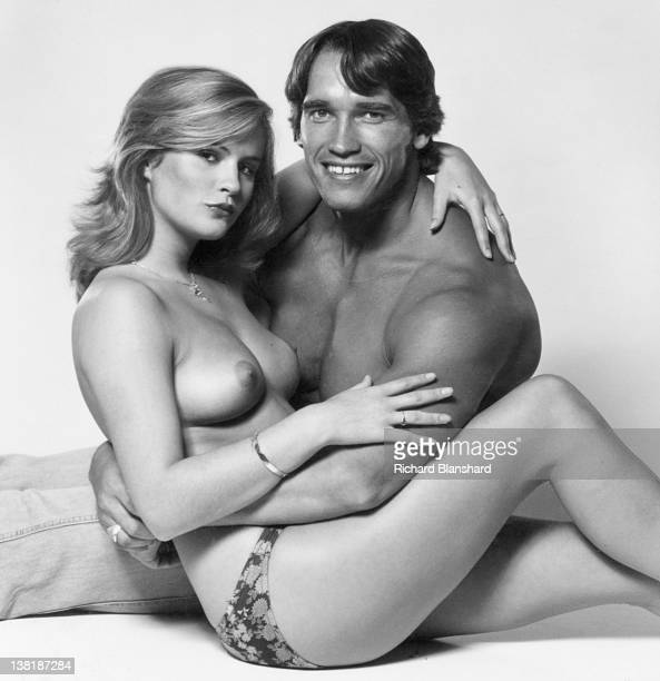 Actor and bodybuilder Arnold Schwarzenegger poses with a topless model circa 1982