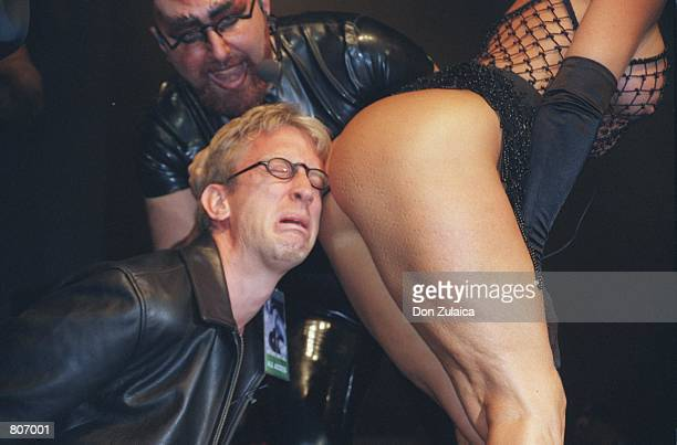 Actor and Comedian Andy Dick rests his head on a participant of the annual 'Exotic Erotic Ball' October 23 1999 in San Francisco CA