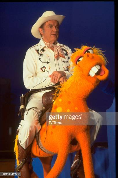 Actor and comedian Bob Hope dressed as a cowboy and riding a puppet horse on the set of The Muppet Show at Elstree Studios, Hertfordshire, circa 1978.