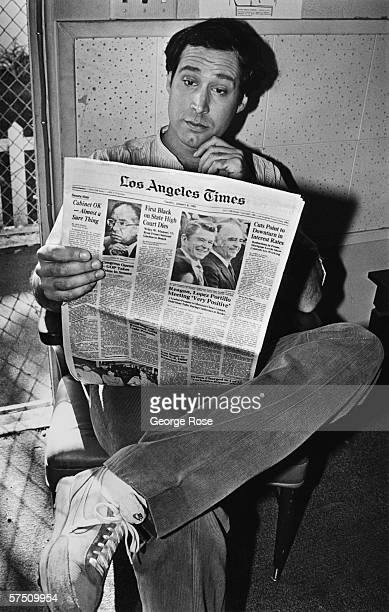 Actor and comedian Chevy Chase reads a newspaper as he takes a break during filming of Under The Rainbow The former star of Saturday Night Live had...