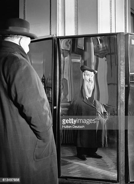 Actor and comedian Oilver Hardy gazing into a distorting mirror at Madame Tussaud's in London ca 1930's