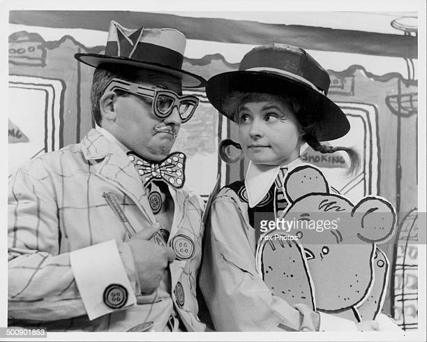 Actor and comedian Ronnie Barker wearing oversized clothes in a skit with an actress circa 1970