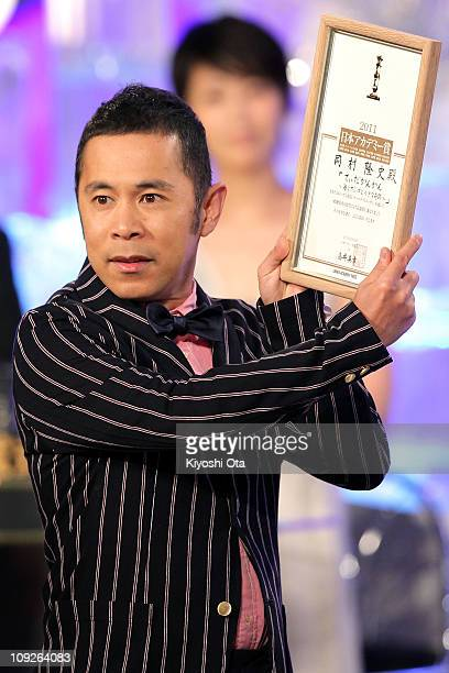 Actor and comedian Takashi Okamura accepts the award for Most Popular Actor for 'Tidakankan Umi to sango to chiisana kiseki ' onstage during the 34th...