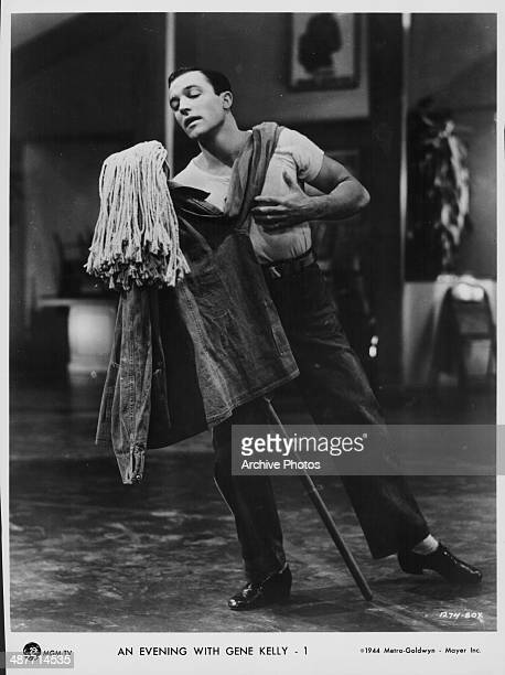 Actor and dancer Gene Kelly dancing with a mop in a scene from the movie 'Thousands Cheer' 1943