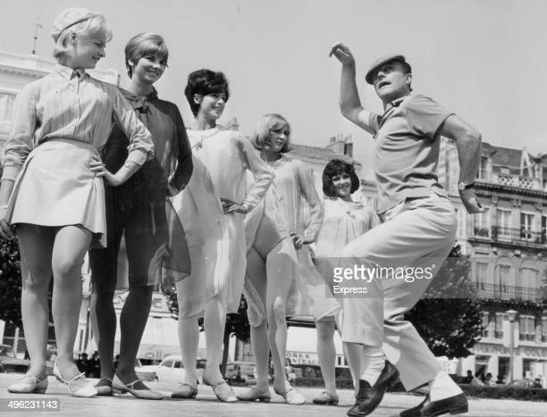 Actor and dancer Gene Kelly posing with a group of young women on a promenade June 15th 1966