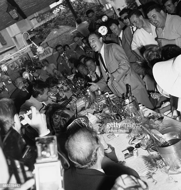 Actor and dancer Gene Kelly surrounded by press photographers as he arrives at the Cannes Film Festival May 4th 1959
